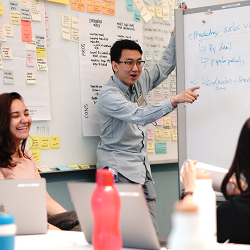 Young man beside a whiteboard presenting to two young women.
