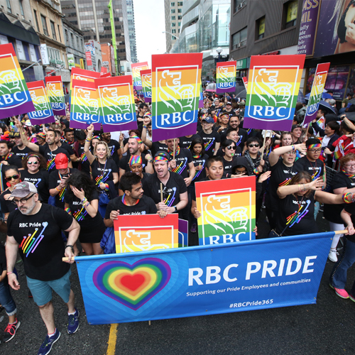 Crowd holding signs and marching during the RBC Pride Parade.