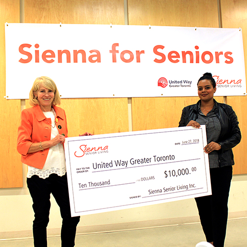 image of Lois handing a cheque in Sienna for Seniors