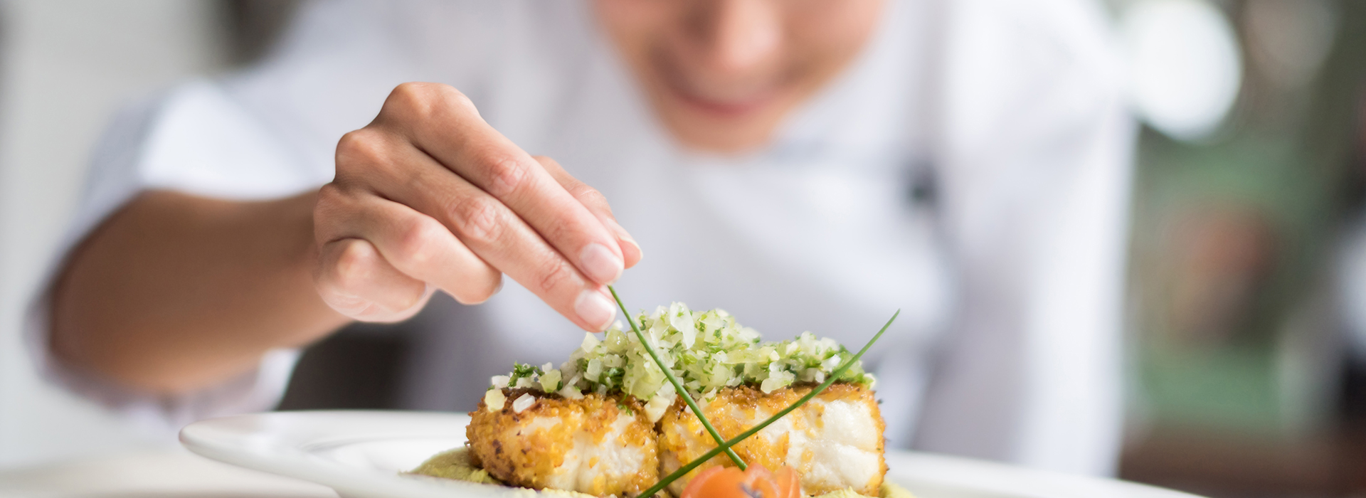 image of a female chef adding final touch to the dish