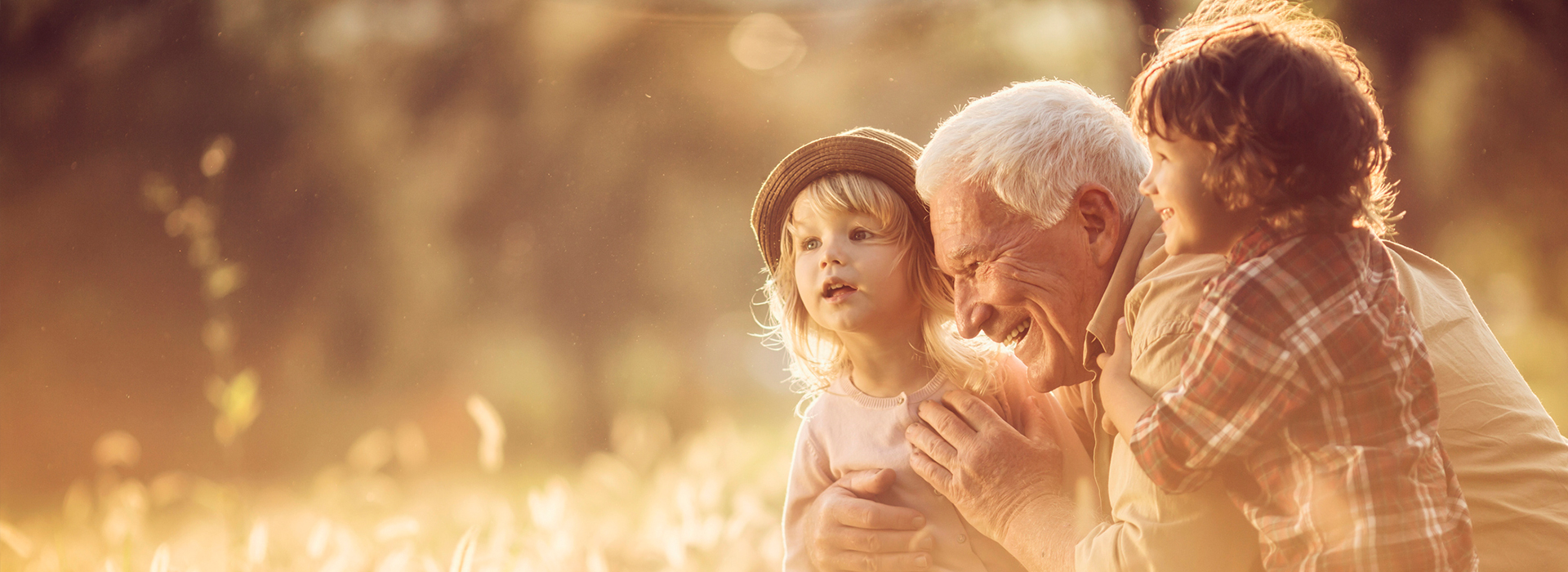 image of a happy male senior having fun with his two grandchildren in an outdoor setting