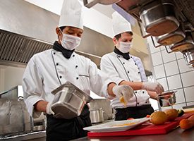 image of two chefs in masks preparing food