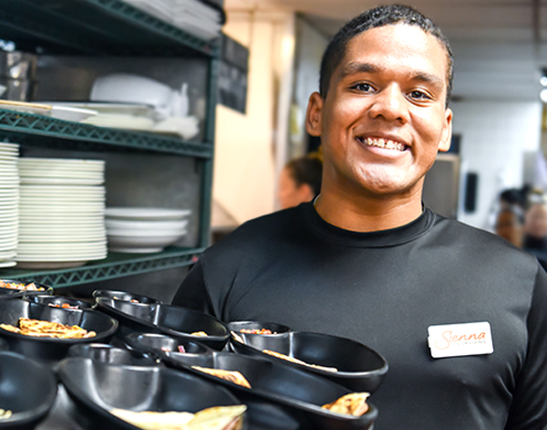 image of a male server smiling and holding a trade of food in a kitchen setting