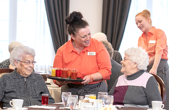 image of a server smiling with the residents together in the dining room