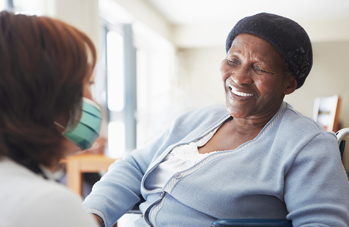 image of an African female senior smiling towards a nurse in mask
