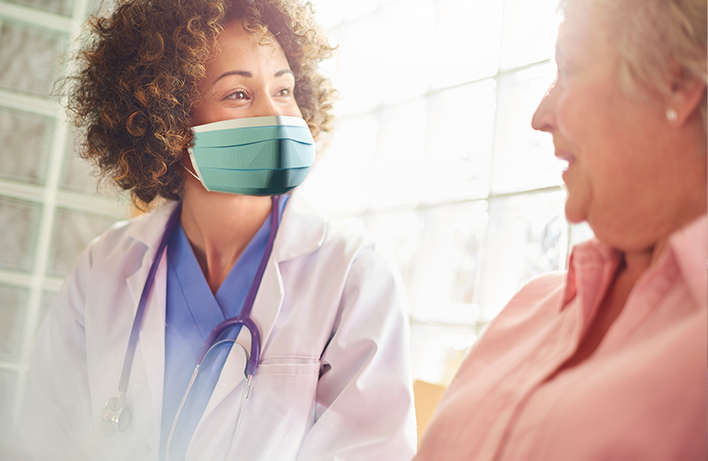 image of a medical worker wearing mask and looking at a female senior