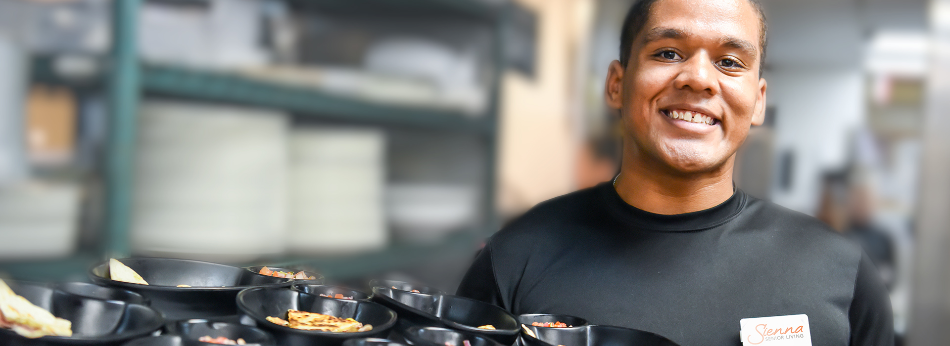 image of a male server holding a tray of food and smiling towards the camera