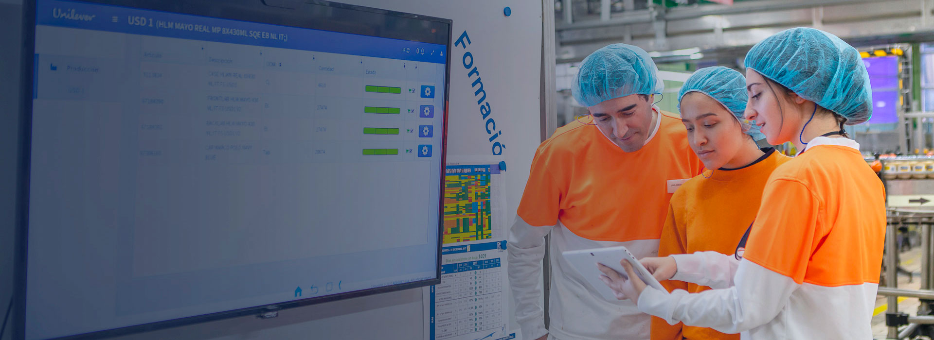 Group of factory workers discussing work on iPad with large wall screen next to them showing data