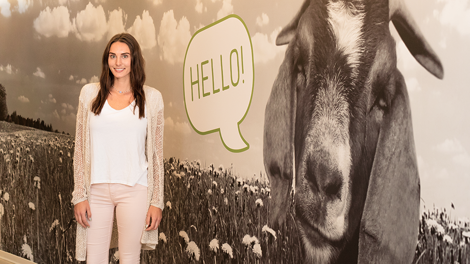 "Team Member Next to Picture of Goat That is Saying ""Hello"""
